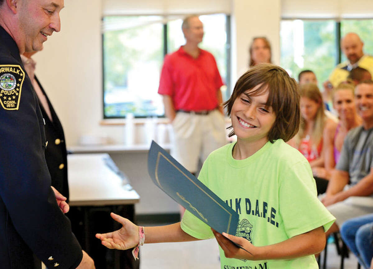 Hour photo / Erik Trautmann Children in the DAREcamp including Aidan DeVingo mark their final day of camp with a graduation at the police headquarters Friday.