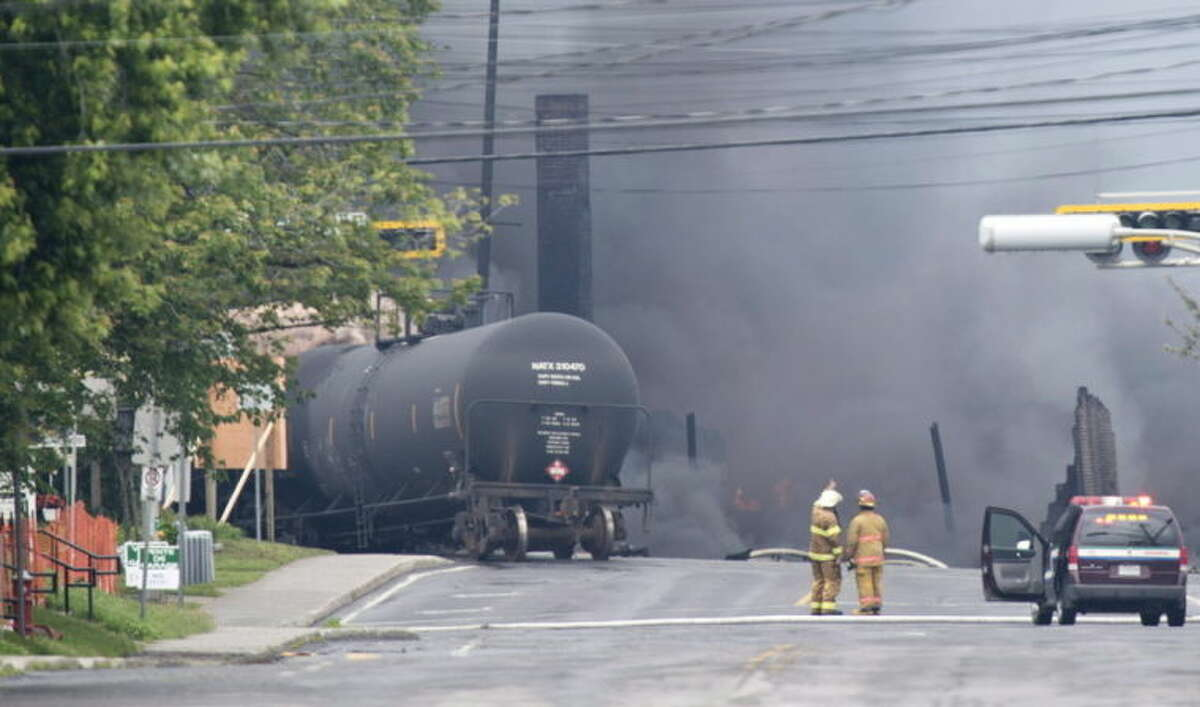 In this Saturday, July 6, 2013 photo, smoke rises from railway cars carrying crude oil after derailing in downtown Lac-Megantic, Quebec. Lac-Megantic still struggles to recover as it marks the disaster's one-year anniversary. (AP Photo/The Canadian Press, Paul Chiasson)