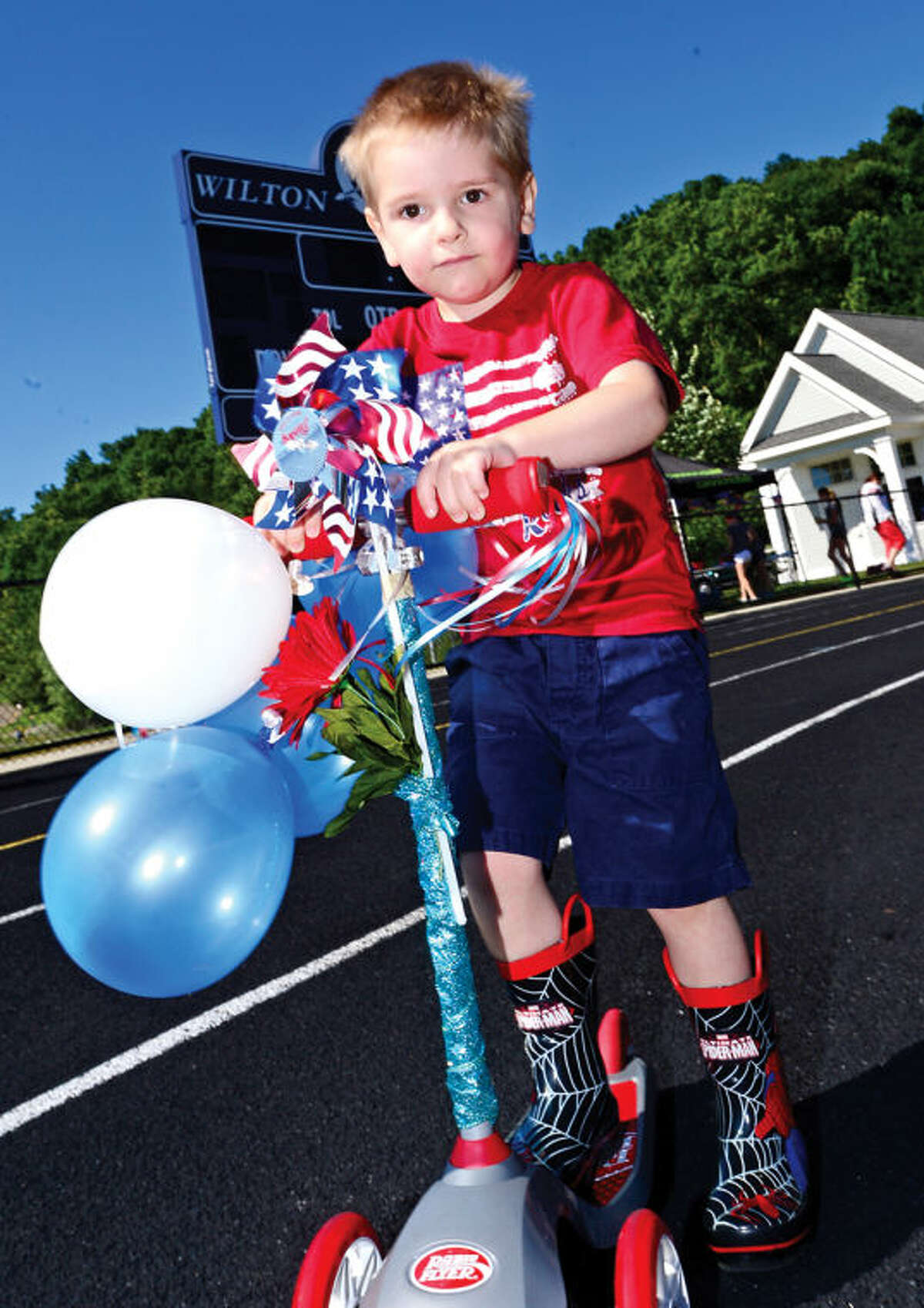 Hour photo / Erik Trautmann Aiden Harrell, 3, participates in the Cannondale Bike Rodeo at Fujitani Field as part of Wilton's Independence Day festivities Saturday.