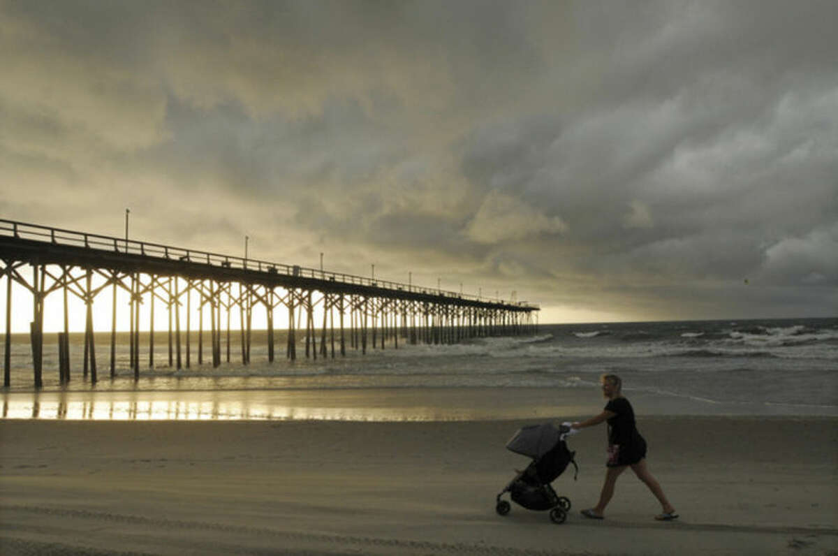 Clouds and rains move in as beachgoers walk along the shore of the north end of Carolina Beach, N.C., Thursday, July 3, 2014. Residents along the coast of North Carolina are bracing for the arrival of the Hurricane Arthur, which threatens to give the state a glancing blow on Independence Day. (AP Photo/Wilmington Star-News, Mike Spencer)