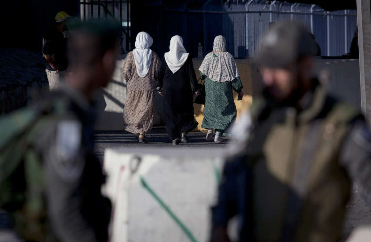 Palestinian women walk through the Qalandia security checkpoint on their way to Jerusalem, behind two Israeli border guards officers, on the outskirts of the West Bank city of Ramallah, Friday, July 4, 2014. (AP Photo/Nasser Nasser)