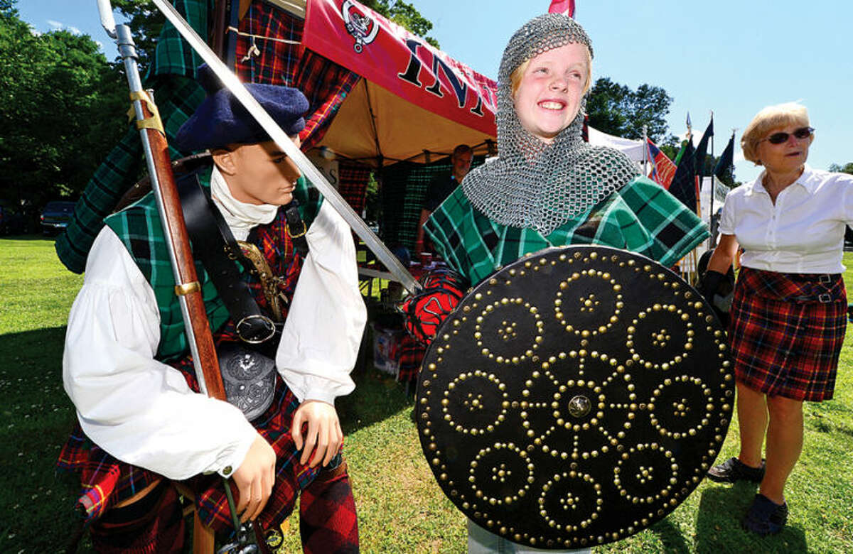 Hour photo / Erik Trautmann Lucy Cunningham dons chain mail at the Clan Village during the 91st Annual Round Hill Highland Games at Cranbury Park Saturday.