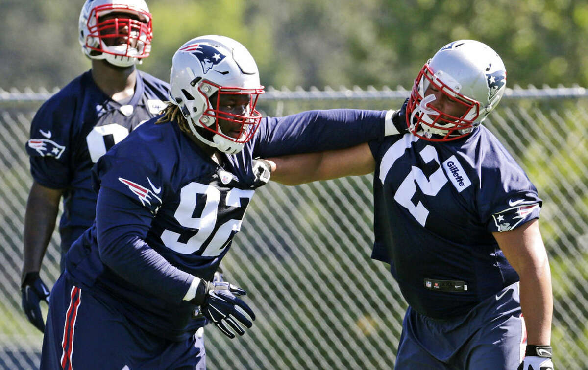New England Patriots defensive tackle Malcolm Brown, left, pushes off on lineman Joe Vellano, right, during an NFL football training camp in Foxborough, Mass., Friday, July 31, 2015. (AP Photo/Charles Krupa)