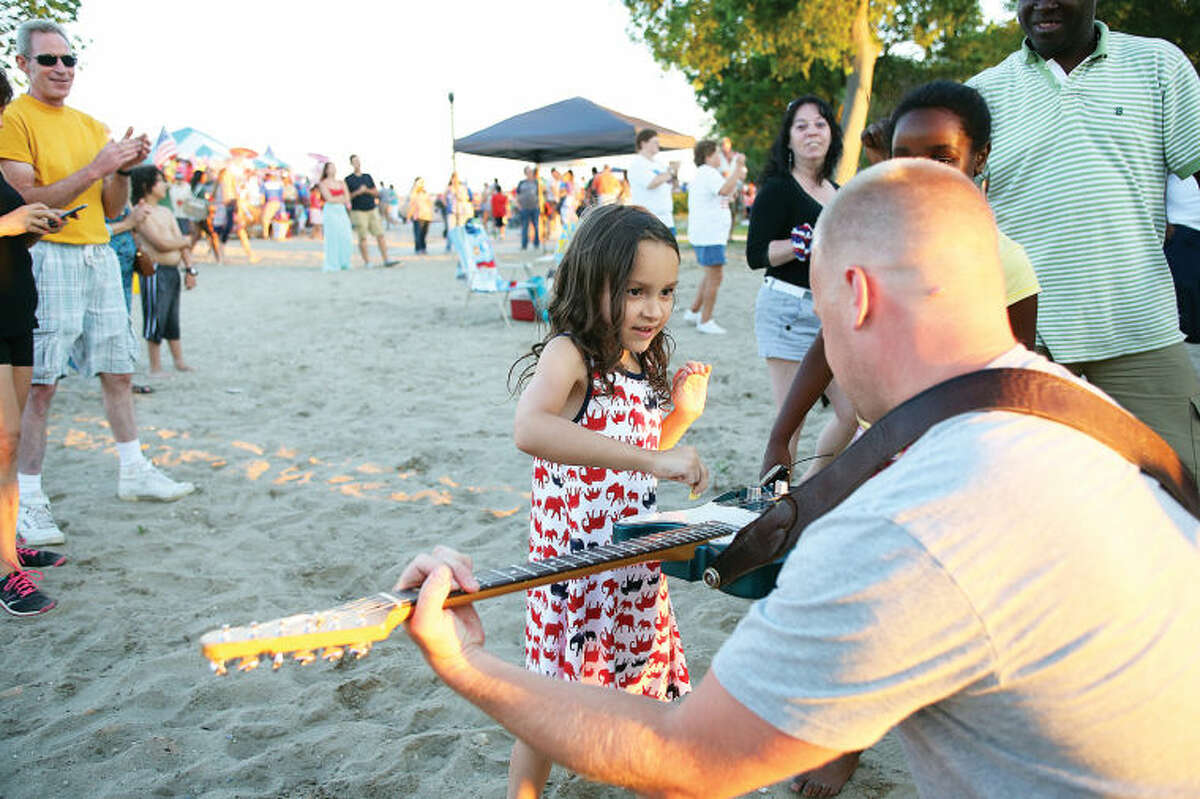 Jimmy & The Parrots let Sofia Gomez , 6, play the guitar before Norwalk's annual firework display at Shady Beach Saturday evening. Hour Photo / Danielle Calloway