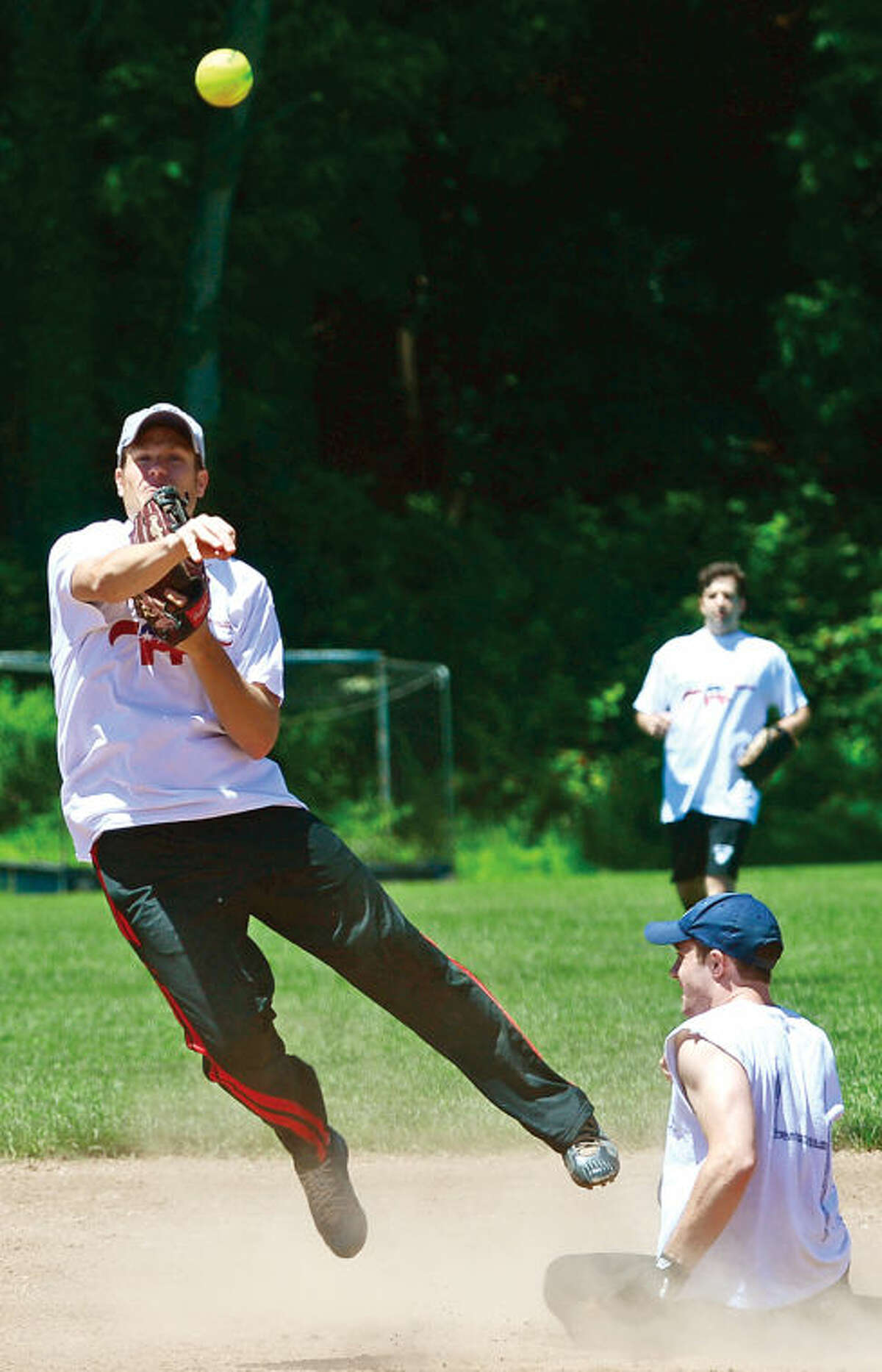 Hour photo / Erik Trautmann Republican Chris Alexander looks to turn two over the head of Democrat Max Fanwick during the annual Wilton Political softball game where town Republicans play Democrats for the Frivolity Cup as part of Wilton's Independence Day Celebration.