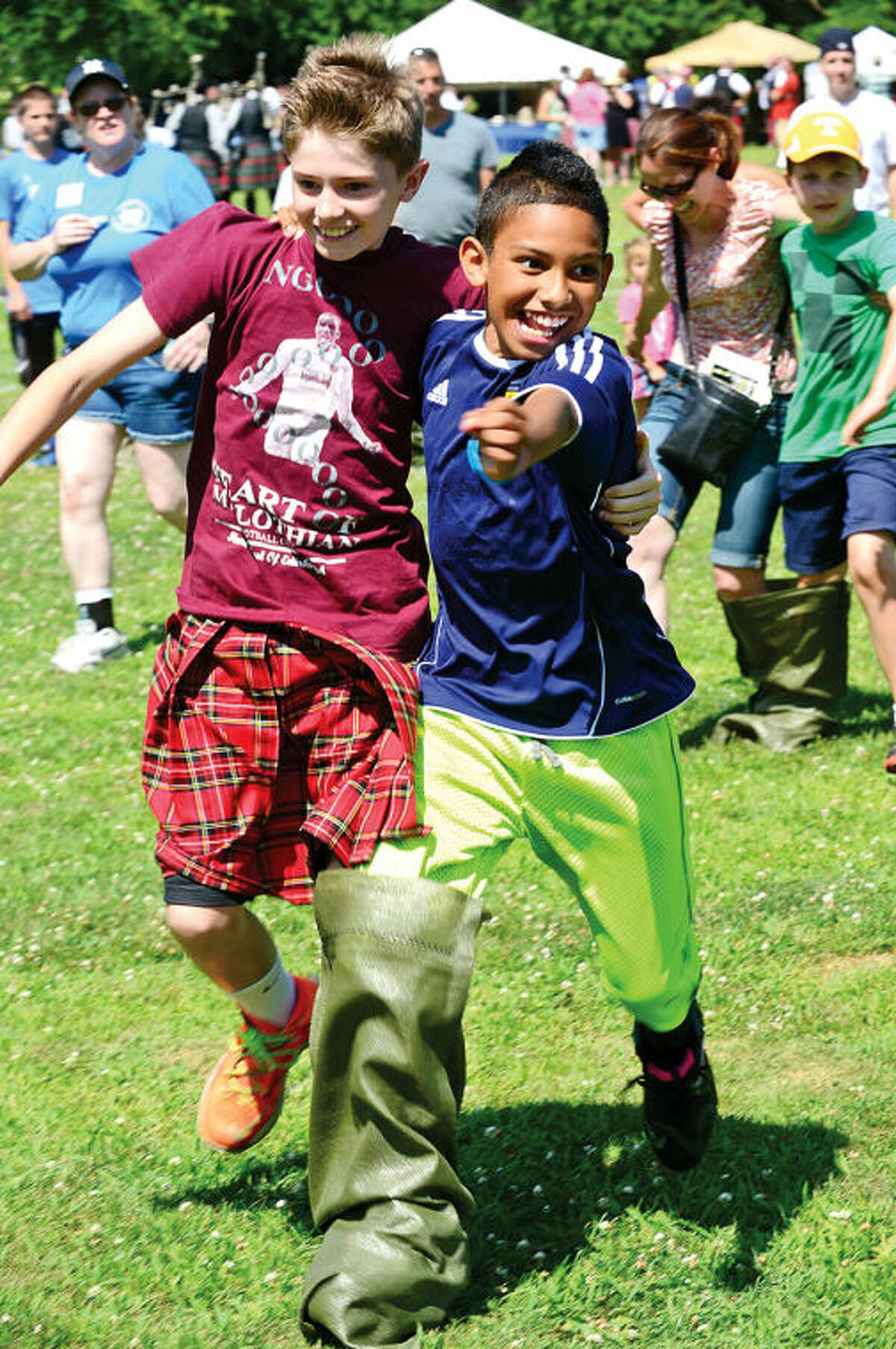 Hour photo / Erik Trautmann Bobby Beaton, 12, and Brennyn Ordoner, 9, come in second during the three-legged race at the 91st Annual Round Hill Highland Games at Cranbury Park Saturday.