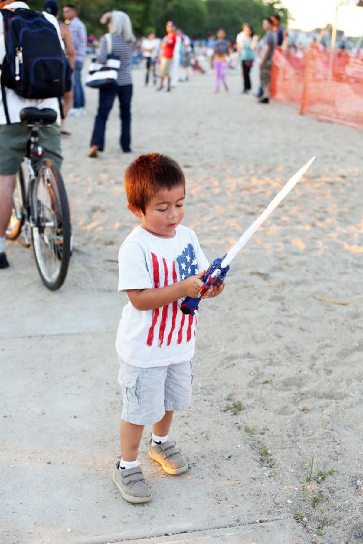 Erik Garcia, 4, plays with a sword before Norwalk's annual firework display at Calf Pasture Beach Saturday evening. Hour Photo / Danielle Calloway