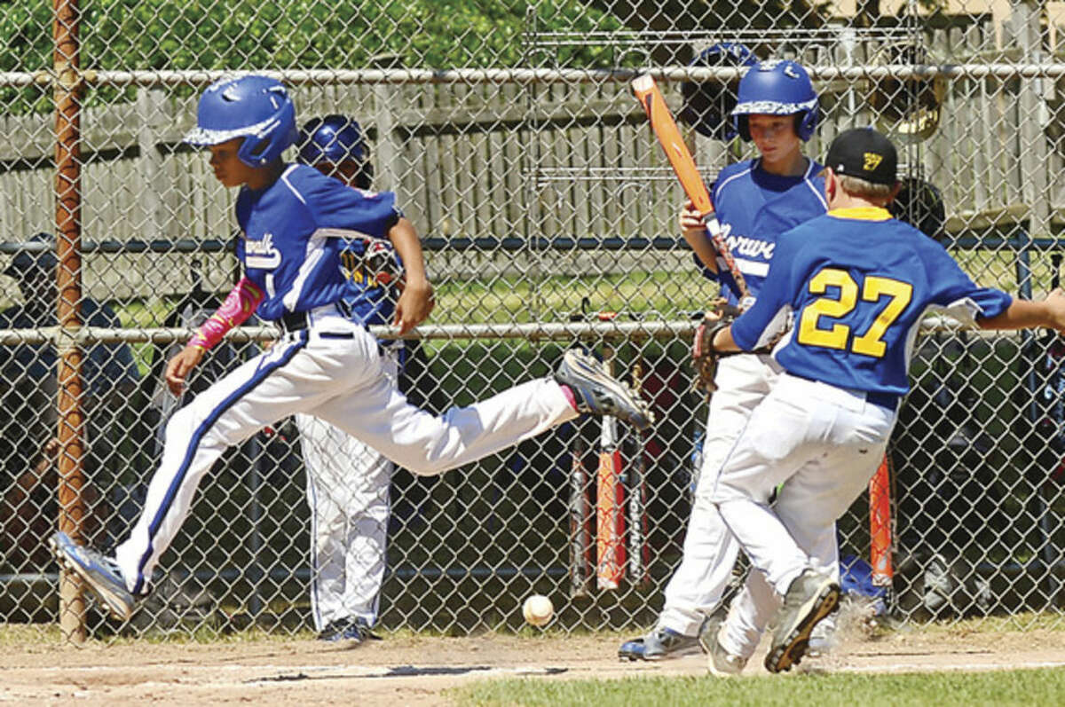 Hour photo/Erik Trautmann Norwalk's AJ Robinson crosses the plate during the Cal Ripken 11s state championship win over Newtown on Saturday.
