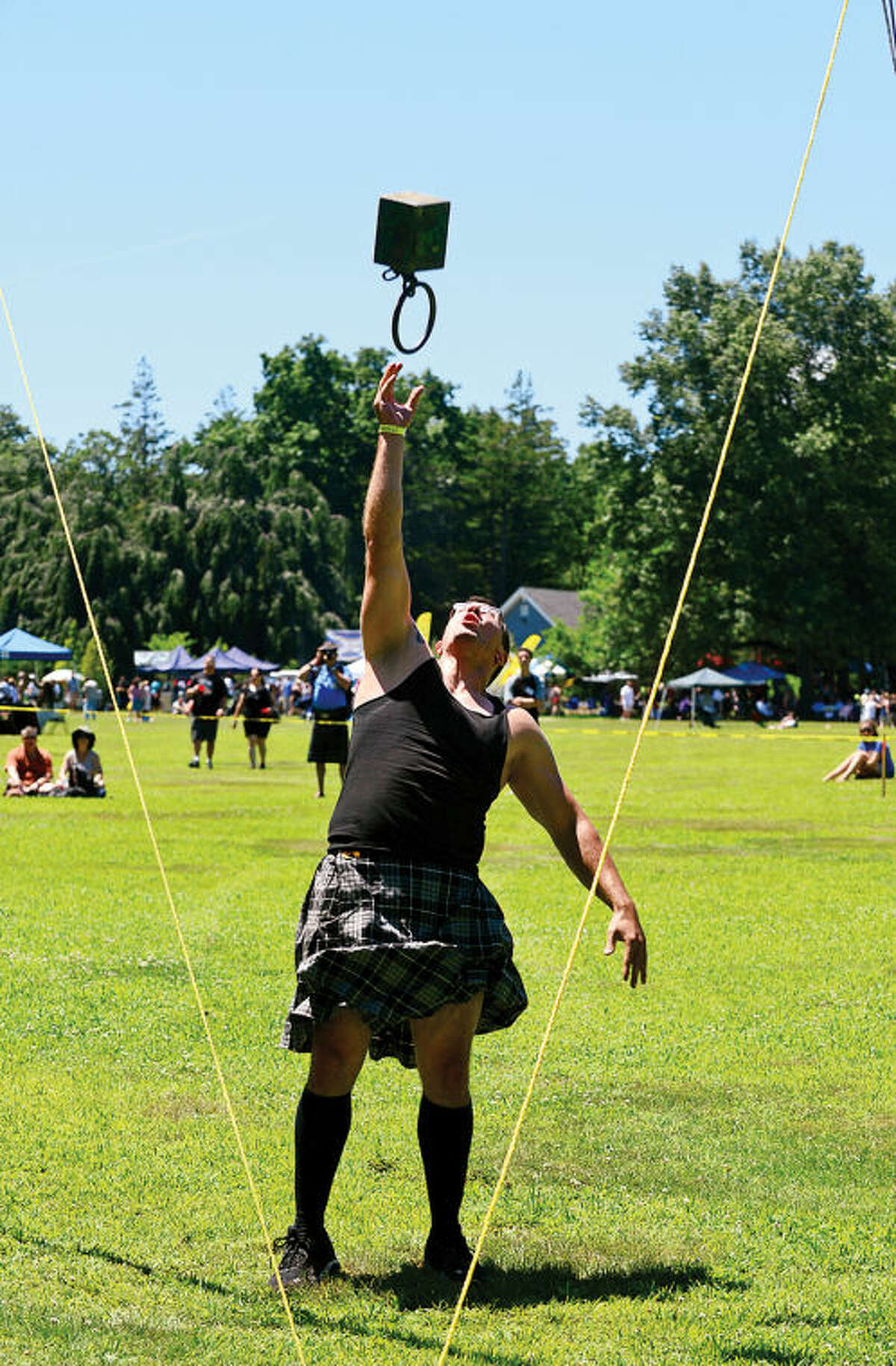 Hour photo / Erik Trautmann Ron Remeika tosses the weight over the bar during the 91st Annual Round Hill Highland Games at Cranbury Park Saturday.