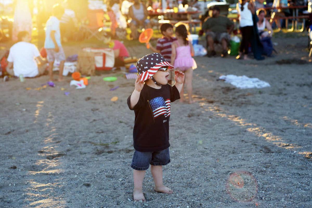Tyler Spence, 2 1/2, enjoys the festivities before Norwalk's annual firework display at Shady Beach Saturday evening. Hour Photo / Danielle Calloway