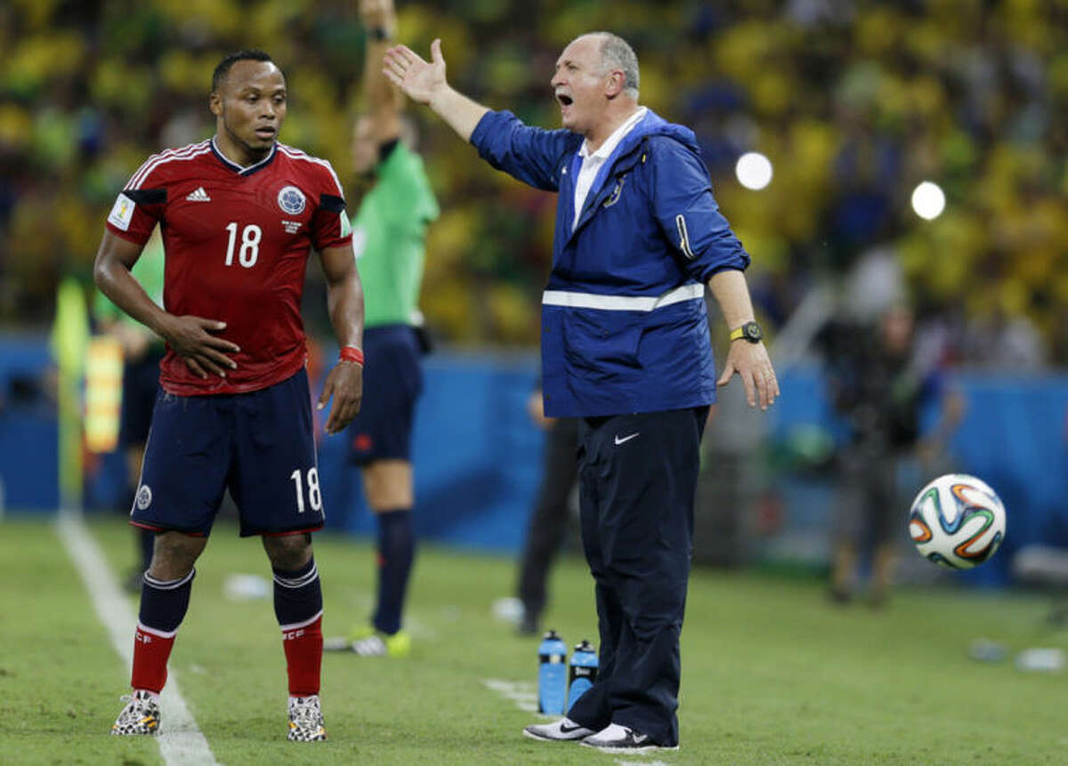 Colombia's Juan Zuniga waits to get the ball as Brazil's coach Luiz Felipe Scolari yells instructions to his players during the World Cup quarterfinal soccer match between Brazil and Colombia at the Arena Castelao in Fortaleza, Brazil, Friday, July 4, 2014. Brazil defeated Colombia 2-1 to advance to the semifinals. (AP Photo/Natacha Pisarenko)
