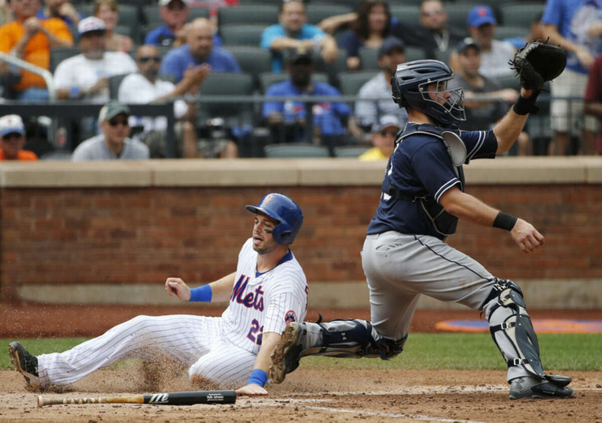 New York Mets' Kevin Plawecki (22) touches the plate scoring on Ruben Tejada's sixth-inning, RBI single as San Diego Padres catcher Austin Hedges, right, waits for the throw in a baseball game in New York, Thursday, July 30, 2015. (AP Photo/Kathy Willens)