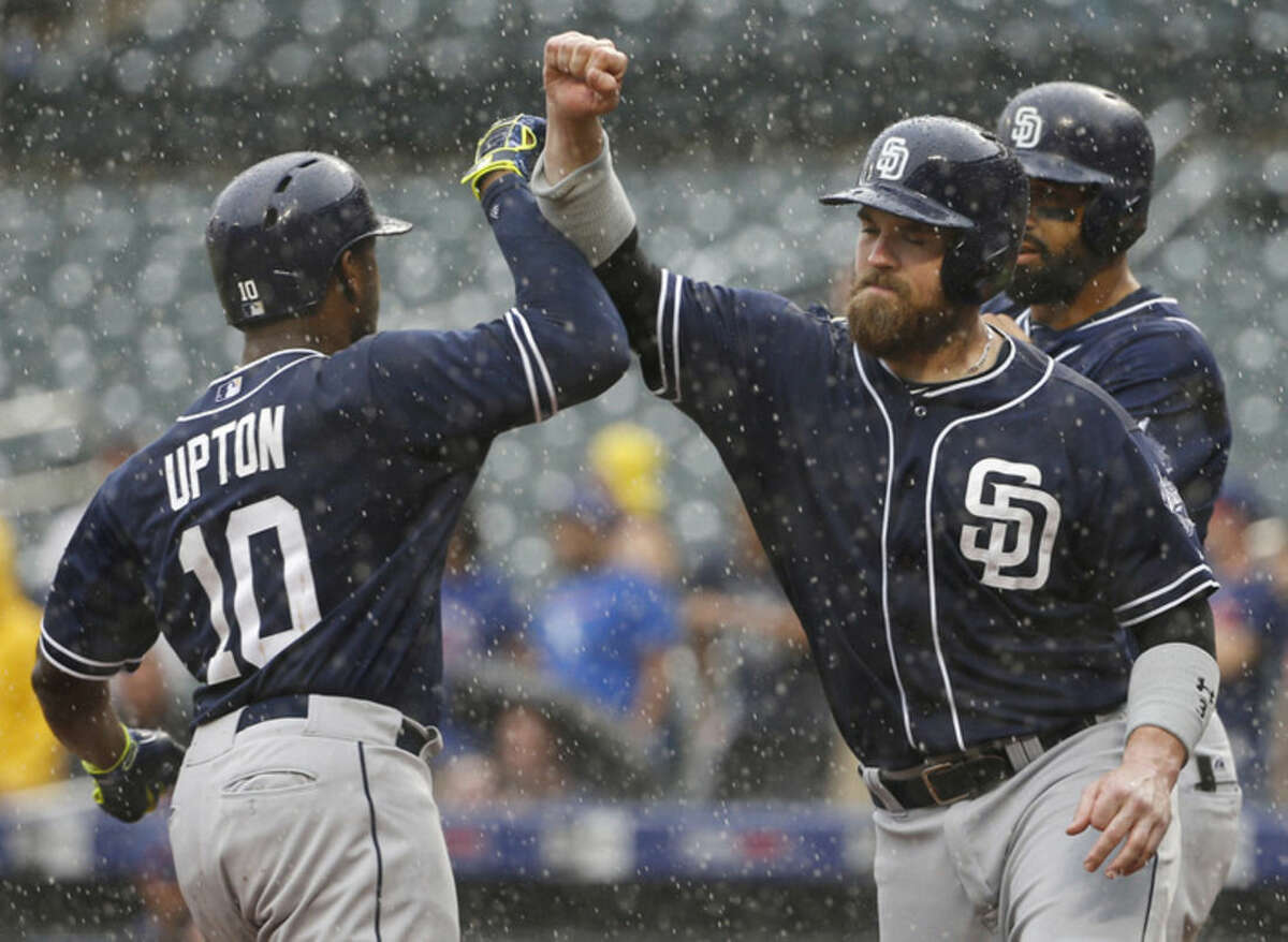 San Diego Padres' Justin Upton (10) greets teammates Derek Norris, center, and Matt Kemp after hitting a ninth-inning, go-ahead, three-run home run off New York Mets relief pitcher Jeurys Familia in a rain-delayed baseball game in New York, Thursday, July 30, 2015. (AP Photo/Kathy Willens)