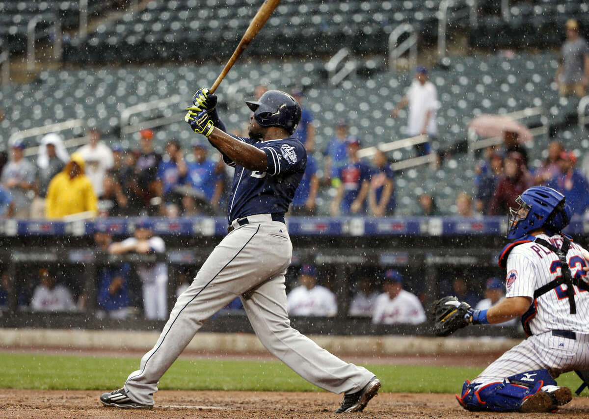 As rain falls, San Diego Padres' Justin Upton, left, hits a ninth-inning three-run home run off New York Mets relief pitcher Jeurys Familia in a baseball game in New York, Thursday, July 30, 2015. Mets catcher Kevin Plawecki (22) watches, right. (AP Photo/Kathy Willens)