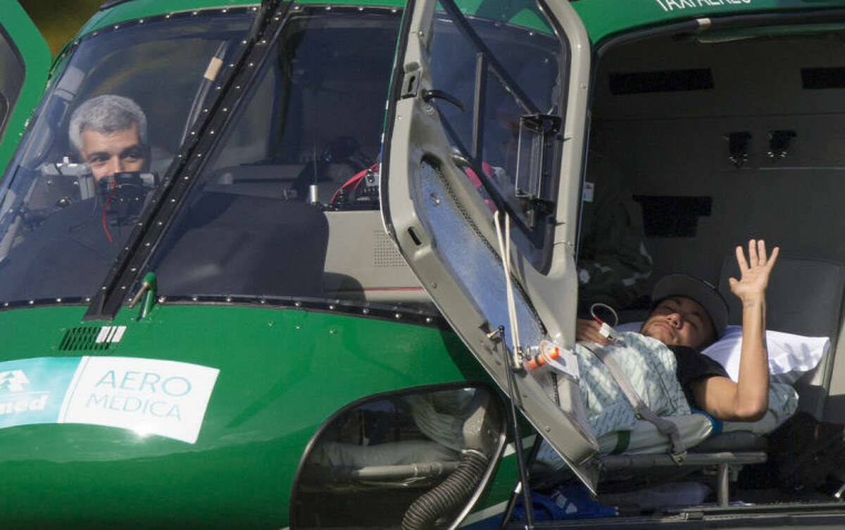 Brazil's Neymar waves from inside a medical helicopter at the Granja Comary training center, in Teresopolis, Brazil, Saturday, July 5, 2014. Neymar was airlifted from Brazil's training camp Saturday and will be treated at home for his back injury. Neymar, the biggest football star in Brazil, was ruled out of the rest of the World Cup after fracturing his third vertebra during Friday's 2-1 quarterfinal win over Colombia. (AP Photo/Leo Correa)