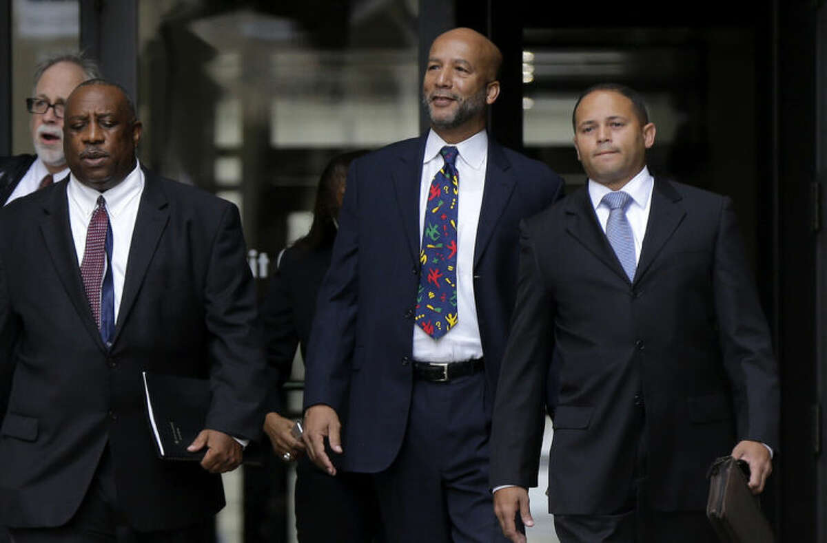 Former New Orleans Mayor Ray Nagin, center, leaves federal court after being sentenced in New Orleans, Wednesday, July 9, 2014. Nagin was sentenced to 10 years in prison for bribery, money laundering and other corruption that spanned his two terms as mayor, including the chaotic years after Hurricane Katrina hit in 2005. He was convicted Feb. 12 of accepting hundreds of thousands of dollars from businessmen who wanted work from the city or Nagin's support for various projects. The bribes came in the form of money, free vacations and truckloads of free granite for his family business. (AP Photo/Gerald Herbert)