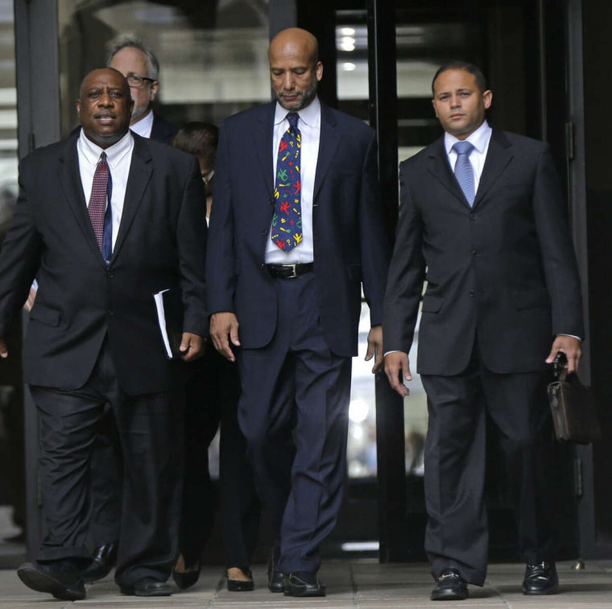 Former New Orleans Mayor Ray Nagin, center, leaves federal court after being sentenced in New Orleans, Wednesday, July 9, 2014. Nagin was sentenced Wednesday to 10 years in prison for bribery, money laundering and other corruption that spanned his two terms as mayor, including the chaotic years after Hurricane Katrina hit in 2005. He was convicted Feb. 12 of accepting hundreds of thousands of dollars from businessmen who wanted work from the city or Nagin's support for various projects. The bribes came in the form of money, free vacations and truckloads of free granite for his family business. (AP Photo/Gerald Herbert)