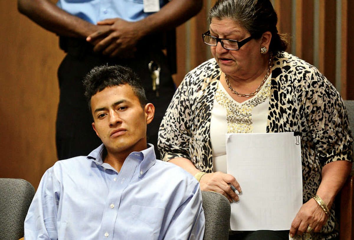 Hour photo / Erik Trautmann Rolando Garcia-Navarro is arraigned with the assistance of a court interpreter for charges of robbery and assault at Norwalk Superior Court Tuesday