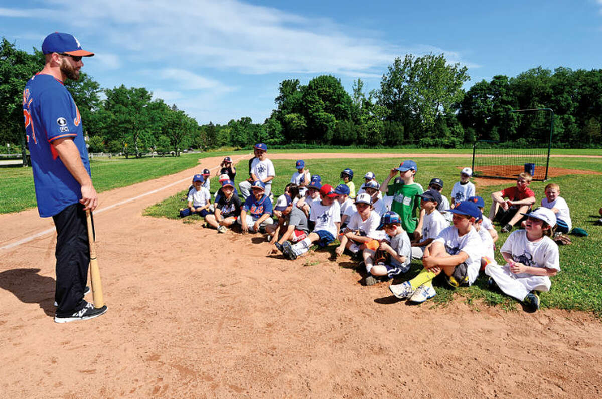Hour photo / Erik Trautmann Major League Baseball player for the New York Mets, Eric Campbell, instructs campers at Baseball World summer camp.