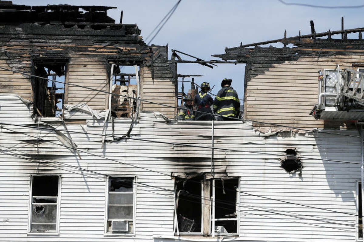 Firefighters work on the top floor inside a burned three-story apartment and business building in Lowell, Mass., Thursday, July 10, 2014, where officials said seven people died in a fast-moving pre-dawn fire. The victims?' names were not immediately made public. The cause and origin of the blaze remain under investigation, State Fire Marshal Stephen Coan said. (AP Photo/Elise Amendola)