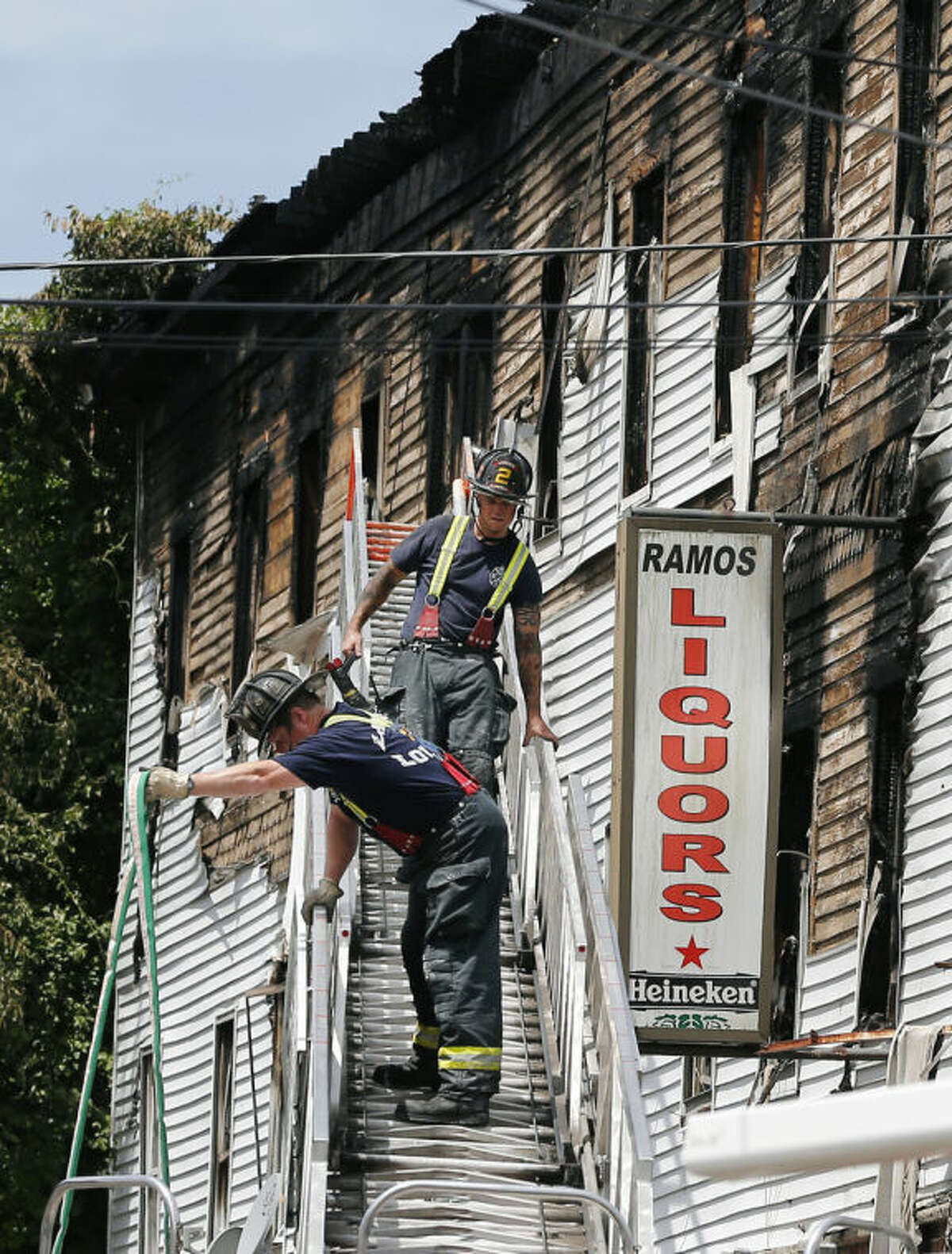 Firefighters work on a ladder outside a burned three-story apartment and business building in Lowell, Mass., Thursday, July 10, 2014, where officials said four adults and three children died in a fast-moving pre-dawn fire. (AP Photo/Elise Amendola)