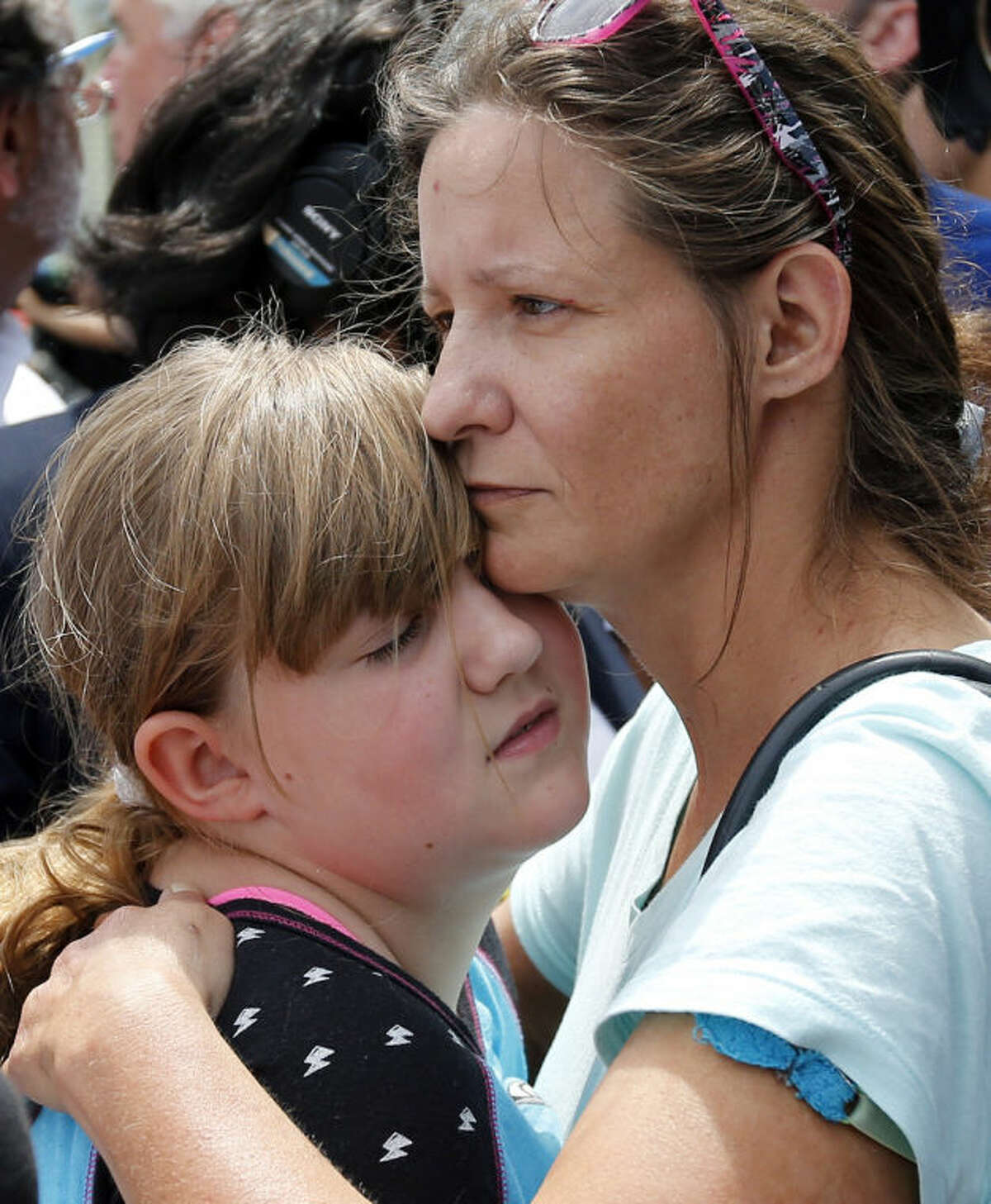 Geri Boyles of Lowell, Mass. hugs her daughter, Corinna, 10, outside a burned three-story apartment and business building in Lowell, Thursday, July 10, 2014. The neighbors lost people they knew in the fast-moving pre-dawn fire where officials said seven people died. (AP Photo/Elise Amendola)