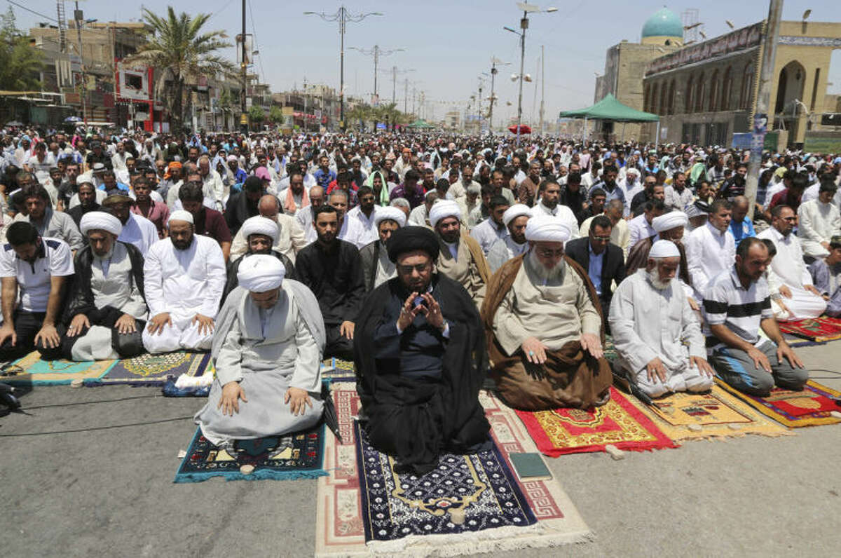 Followers of Shiite cleric Muqtada al-Sadr attend open-air Friday prayers in the Shiite stronghold of Sadr City, Baghdad, Iraq, Friday, July 11, 2014. The lightning sweep by the militants over much of northern and western Iraq the past month has dramatically hiked tensions between the country's Shiite majority and Sunni minority. At the same time, splits have grown between the Shiite-led government in Baghdad and the Kurdish autonomous region in the north. (AP Photo/Karim Kadim)
