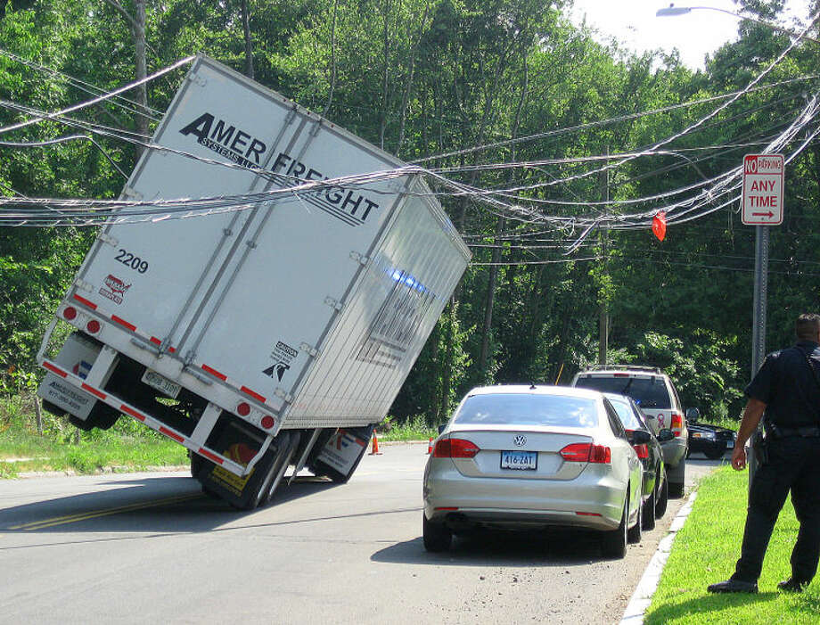 Hour photo / Chris Bosak A truck came to an abrupt and dangerous stop on Norden Place Friday morning after hitting wires. The road was closed.