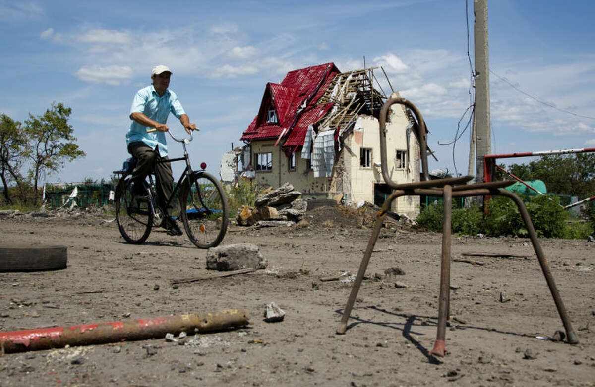 A man rides a bike past a house damaged during fighting, outside the city of Slovyansk, Donetsk Region, eastern Ukraine Thursday, July 10, 2014. In the past two weeks, Ukrainian government troops have halved the amount of territory held by the rebels. Now they are vowing a blockade of Donetsk. In another sign of deteriorating morale among rebels, several dozen militia fighters in Donetsk abandoned their weapons and fatigues Thursday, telling their superiors they were returning home. (AP Photo/Dmitry Lovetsky)
