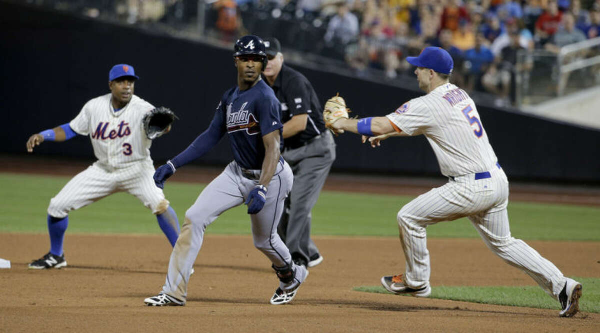 Atlanta Braves' B.J. Upton, center, is caught in a rundown between New York Mets right fielder Curtis Granderson (3) and third baseman David Wright (5) in the sixth inning of a baseball game, Wednesday, July 9, 2014, in New York. Upton was tagged out on the play to end the inning.(AP Photo/Julie Jacobson)
