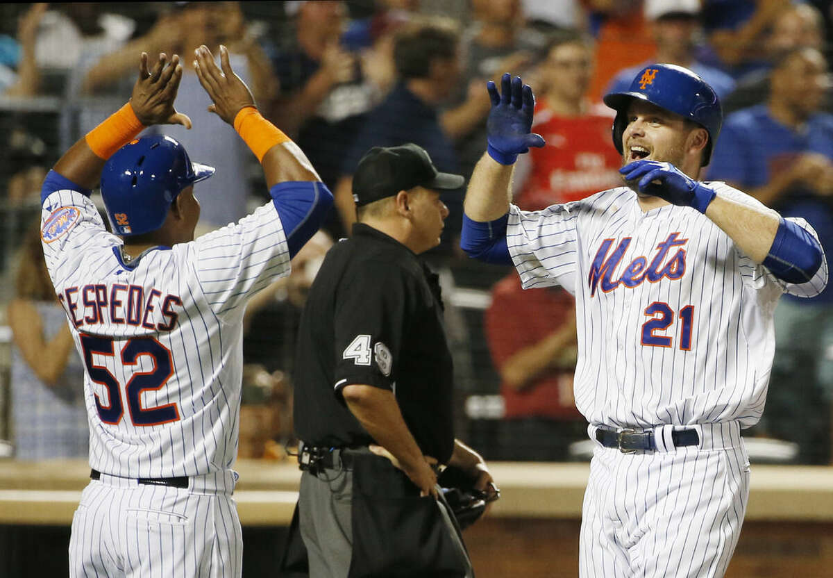 New York Mets Yoenis Cespedes, (52), greets New York Mets Lucas Duda at the plate after scoring on Duda's third-inning, two-run home run during a baseball game against the Washington Nationals in New York, Sunday, Aug. 2, 2015. (AP Photo/Kathy Willens)