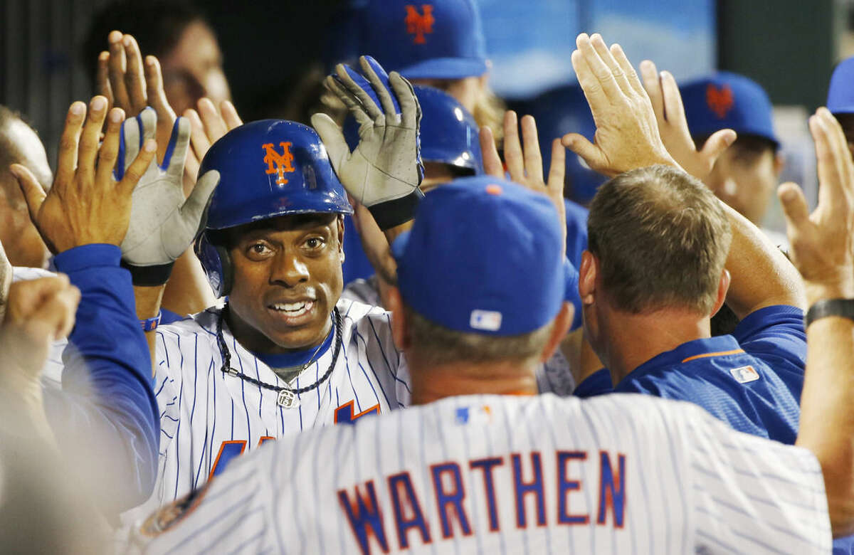 New York Mets Curtis Granderson, left, greets pitching coach Dan Warthen, foreground, in the dugout after hitting a third-inning, two-run, home run during a baseball game in New York on Sunday, Aug. 2, 2015. (AP Photo/Kathy Willens)