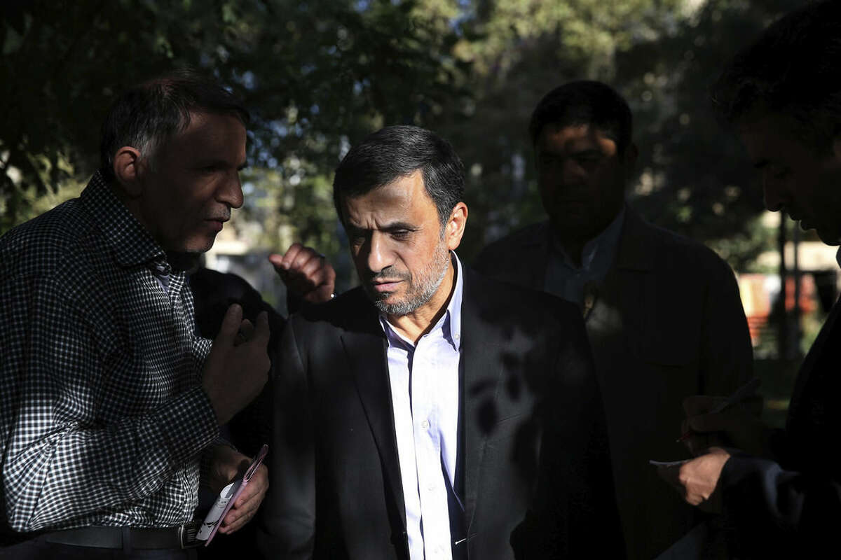 Former Iranian President Mahmoud Ahmadinejad, center, talks with a man after receiving his petition for help outside his house in northeastern Tehran, Iran, Monday, Aug. 3, 2015. Ahmadinejad receive petitions there to pass on to authorities. He has launched a political campaign ahead of February's parliamentary elections in what could prove a challenge to the moderates behind a landmark nuclear agreement reached last month. (AP Photo/Ebrahim Noroozi)