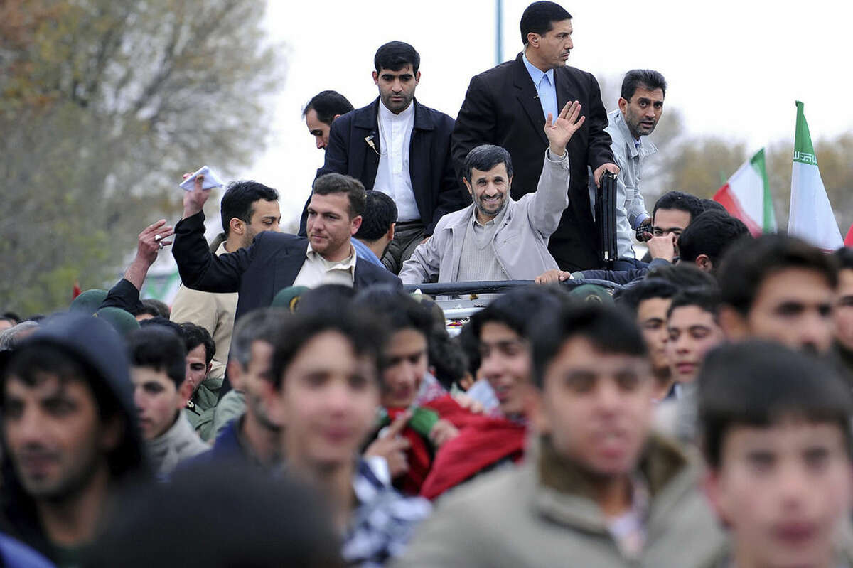 In this photo taken on Nov. 18, 2009, then Iranian President Mahmoud Ahmadinejad, center, waves to his well-wishers from his car during a public welcoming ceremony for him upon his arrival at the northwestern city of Tabriz, Iran. Ahmadinejad has launched a political campaign ahead of parliamentary elections in February 2016 in what could prove a challenge to the moderates behind a landmark nuclear agreement reached last month. (AP Photo/Ebrahim Noroozi)