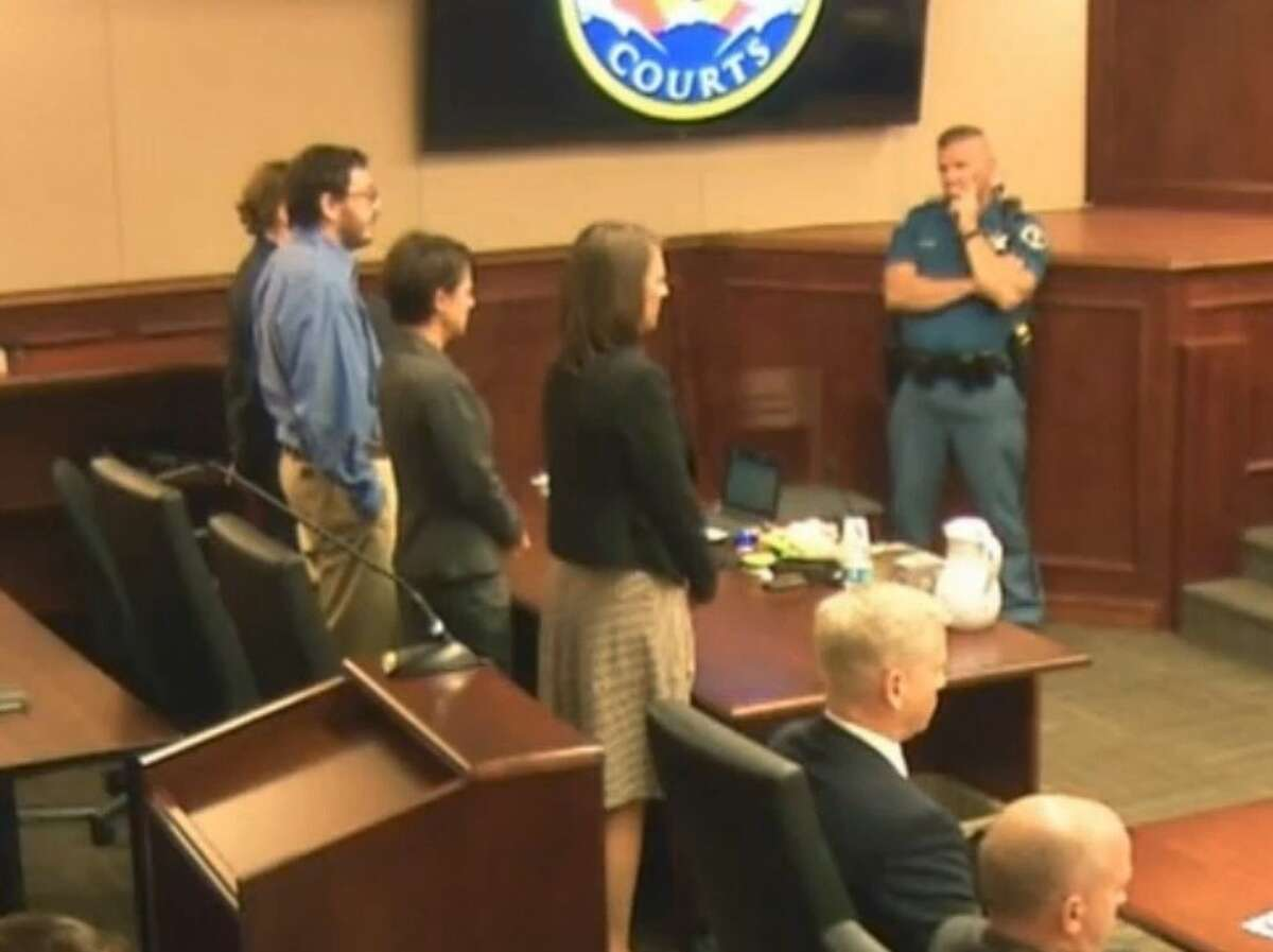 In this image made from Colorado Judicial Department video, James Holmes, second from left in blue shirt, stands with his defense team as Judge Carlos A. Samour, Jr., reads the jury's sentencing verdict in the Colorado theater shooting trial in Centennial, Colo., on Monday, Aug. 3, 2015. (Colorado Judicial Department via AP)