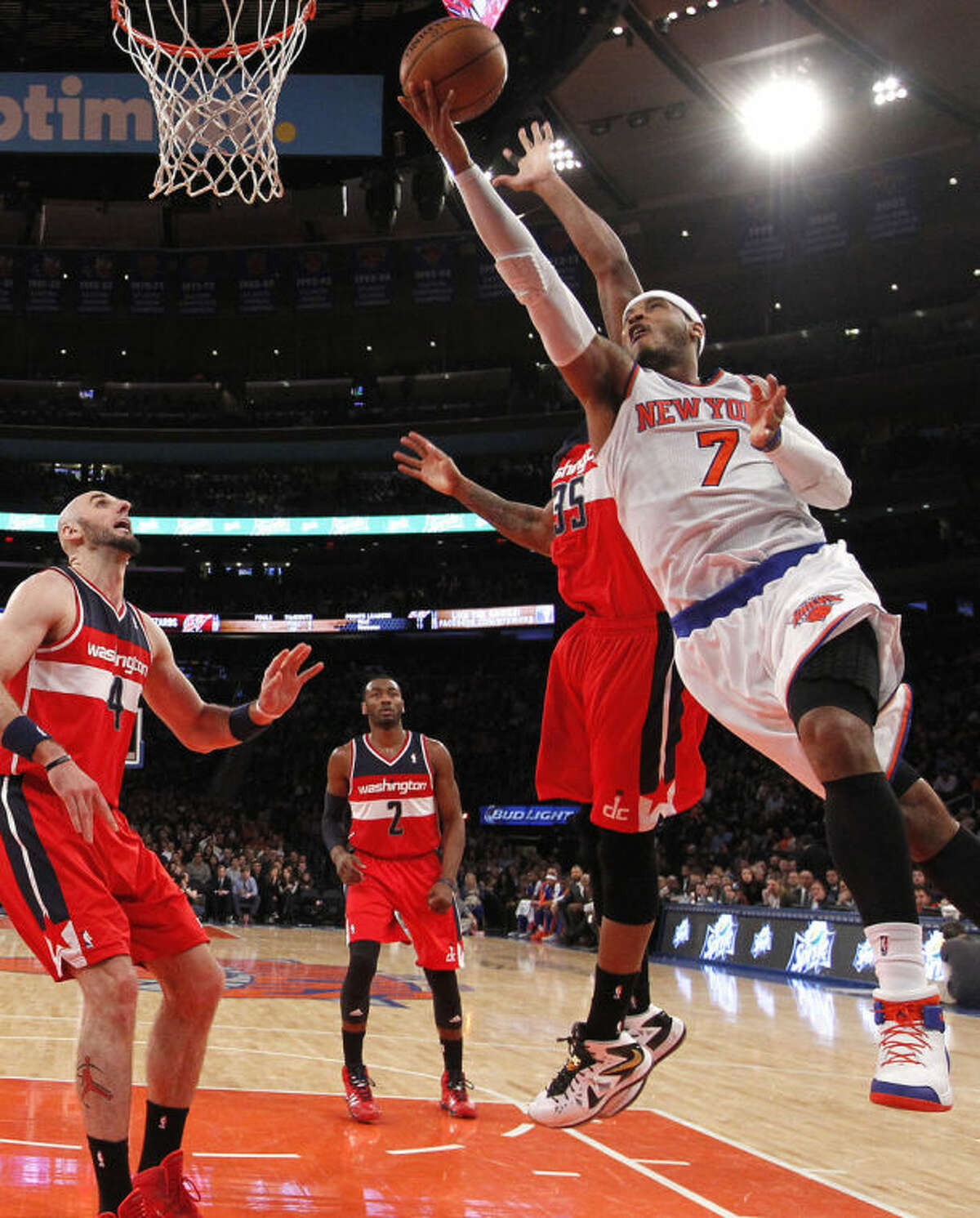FILe - In this Dec. 16, 2013 file photo, New York Knicks' Carmelo Anthony (7) goes to the basket against Washington Wizards' Trevor Booker (35) during the first half of an NBA basketball game in New York. Signing day has arrived in the NBA, if the biggest free agents care to grab their pens. But it?'s unclear if Carmelo Anthony, Chris Bosh and Dwyane Wade _ who all might be waiting on LeBron James to go first _ are ready.(AP Photo/Jason DeCrow, File)