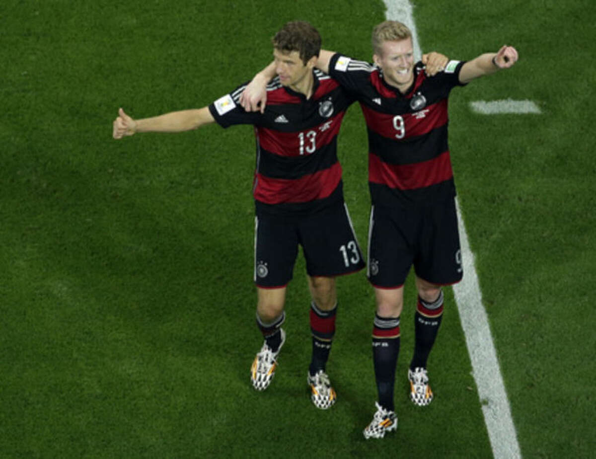 Germany's Andre Schuerrle, right, celebrates with teammate Thomas Mueller after scoring his side's 6th goal during the World Cup semifinal soccer match between Brazil and Germany at the Mineirao Stadium in Belo Horizonte, Brazil, Tuesday, July 8, 2014. (AP Photo/Felipe Dana, Pool)