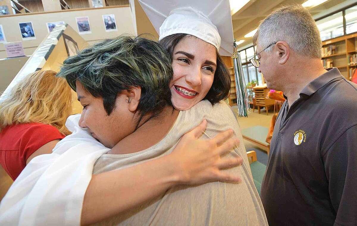 Hour Photo/Alex von Kleydorff Ianina Hernandez gets a hug from her best friend Eduardo Garcia as she graduates from Norwalk High School's Class of 2015 Summer Graduation