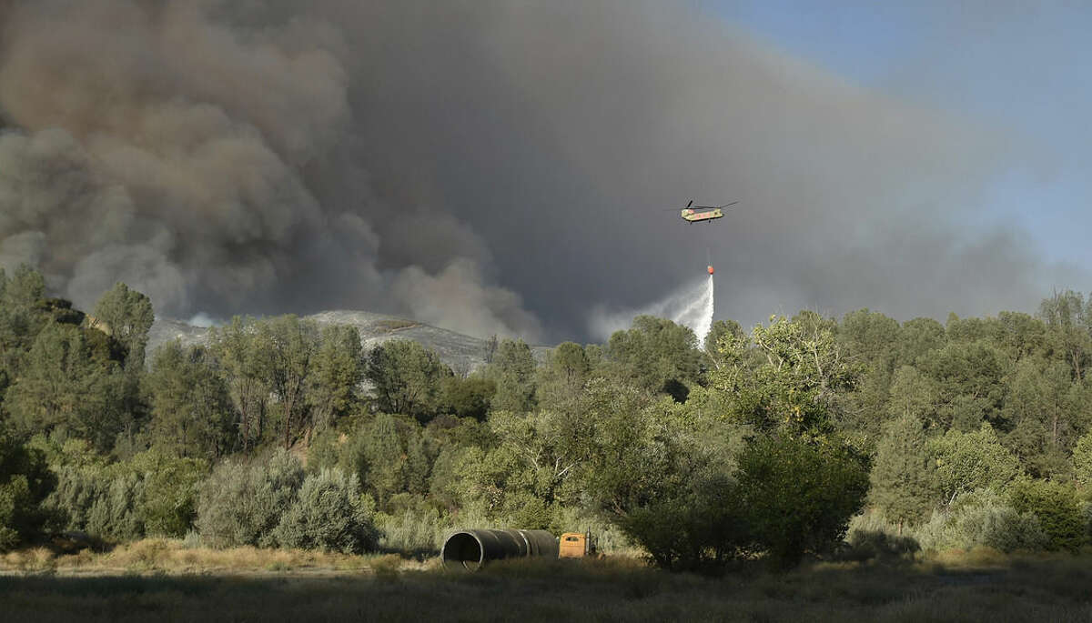 A helicopter drops water on a burning hillside while battling the Rocky Fire near Clearlake, Calif., Monday, Aug. 3, 2015. The fire has charred more than 60,000 acres and destroyed at least 24 residences. (AP Photo/Josh Edelson)