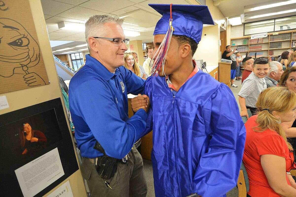 Hour Photo/Alex von Kleydorff Marquise Alexander gets a congratulations from Officer Patrick English as he graduates from Brien McMahon's High School's Class of 2015 Summer Graduation