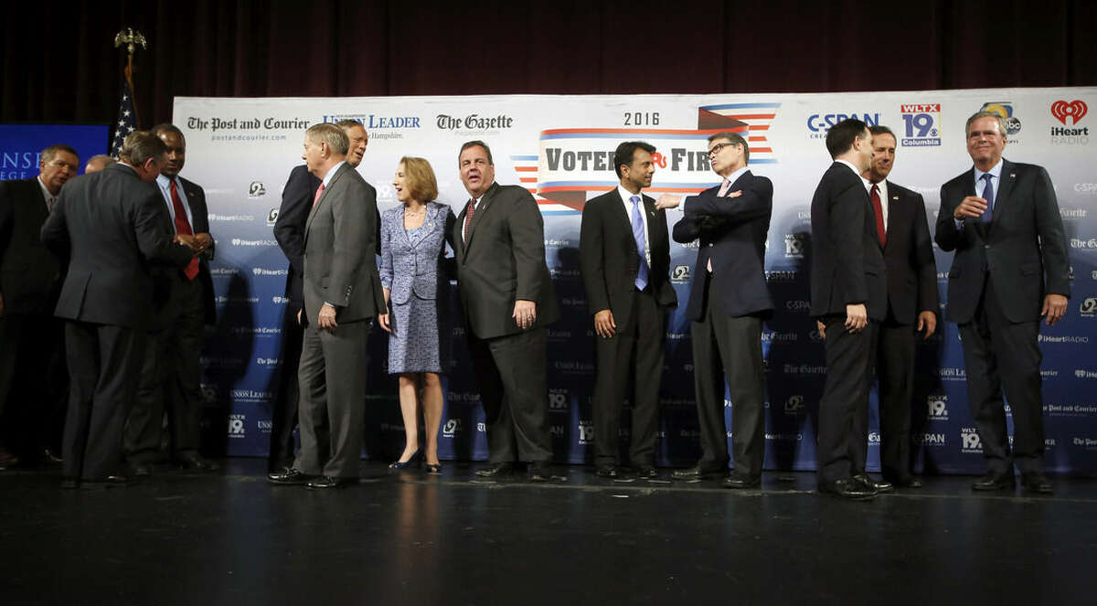 Republican presidential candidates John Kasich, left, Ben Carson, third from left, Lindsey Graham, George Pataki, Carly Fiorina, Chris Christie, Bobby Jindal, Rick Perry, Scott Walker, Rick Santorum and Jeb Bush speak among themselves after a forum Monday, Aug. 3, 2015, in Manchester, N.H. Second from left is Saint Anselm College president Steven DiSalvo. (AP Photo/Jim Cole)