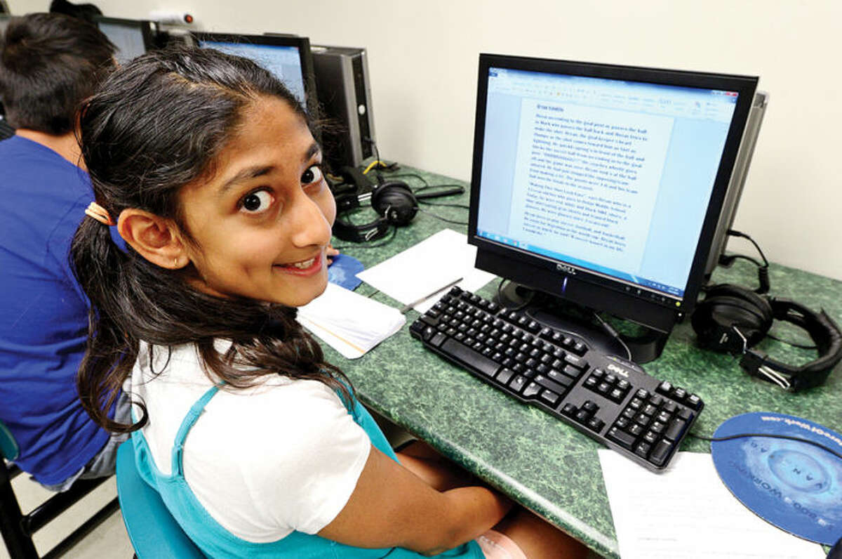 Westhill High School alumni created Project Lede, a summer program that teaches journalism to middle school students, including 11-year-old Arya Bhoghte, during a session at Toquam Magnet School Friday. The program also teaches the middle schoolers how to create a student newspaper.