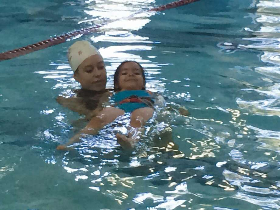 YMCA lifeguard Joanna Korsch, left, teaches a child how to float in water during a swimming safety session at the pool of the Wilton Family YMCA branch.