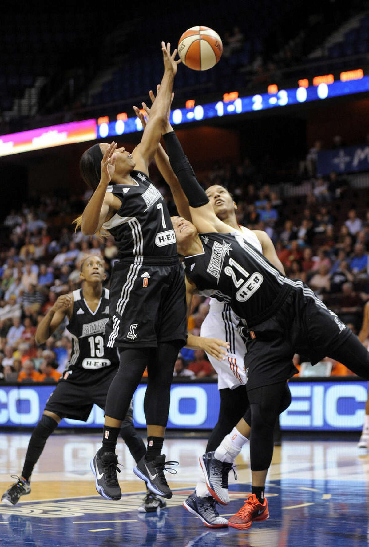San Antonio Stars's Jia Perkins (7) and Kayla McBride (21) fight for a rebound with Connecticut Sun's Alyssa Thomas (25) during the first half of a WNBA basketball game in Uncasville, Conn., on Tuesday, Aug. 4, 2015. (AP Photo/Fred Beckham)