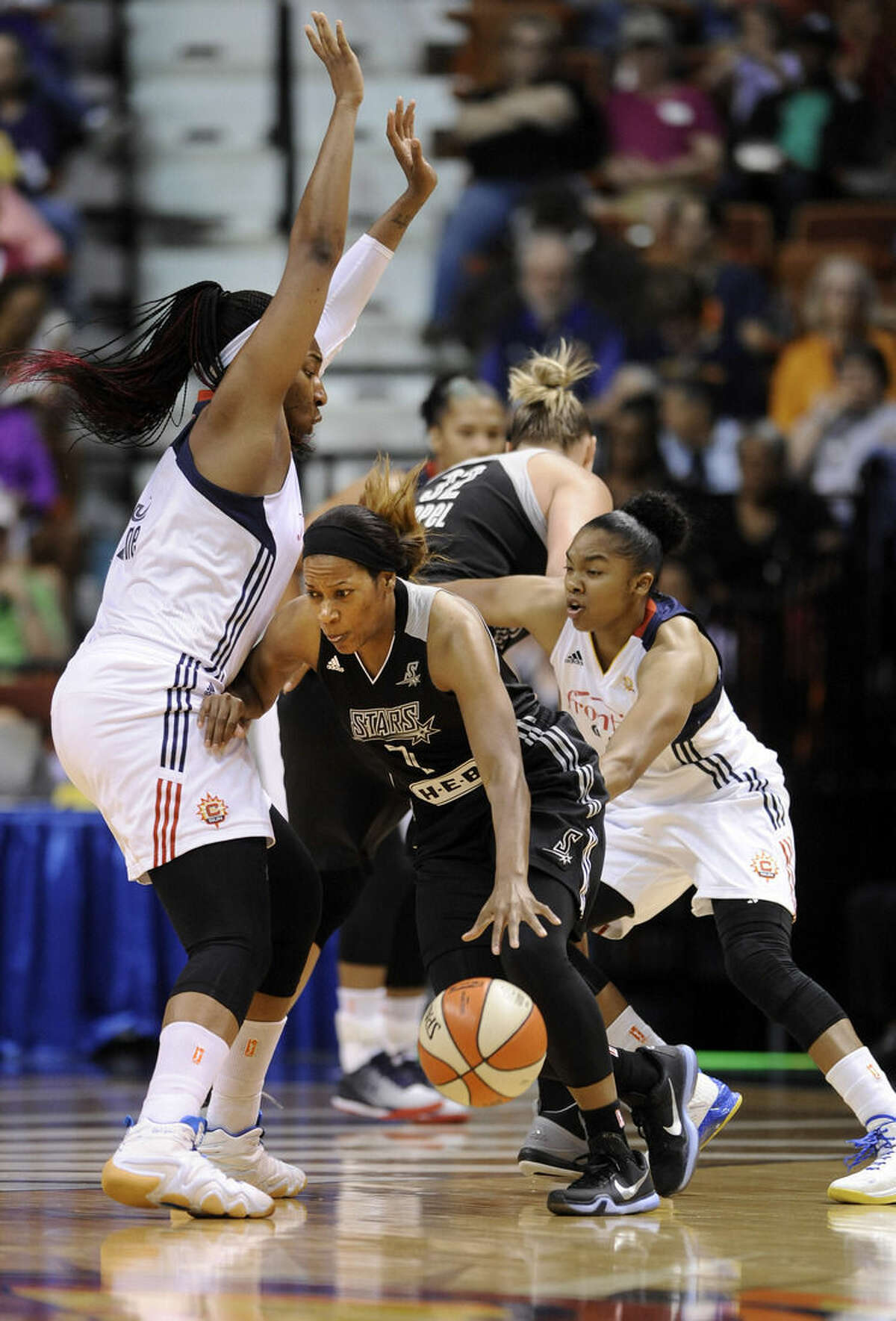 San Antonio Stars's Jia Perkins (7) drives past Connecticut Sun's Kelsey Bone (3) during the first half of a WNBA basketball game in Uncasville, Conn., on Tuesday, Aug. 4, 2015. (AP Photo/Fred Beckham)