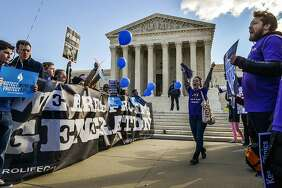 Anti-abortion demonstrators and abortion rights supporters face off outside the Supreme Court.
