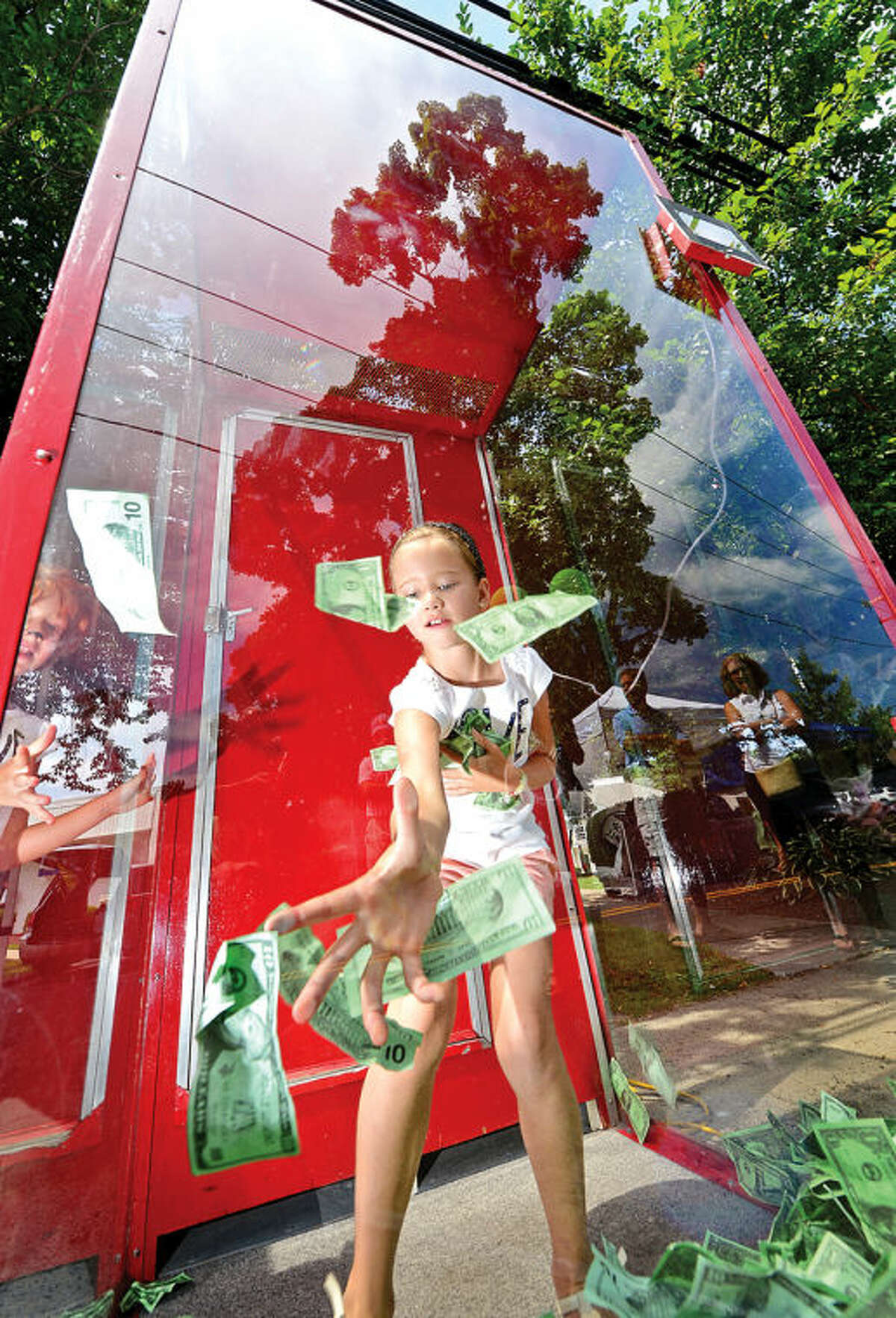 Hour photo / Erik Trautmann Lucia La Orden, 8, tries to grab as many bills as she can to win a raffle prize from Bankwell during the 3rd annual Wilton Street Fair and Sidewalk Sale in Wilton Center Saturday.
