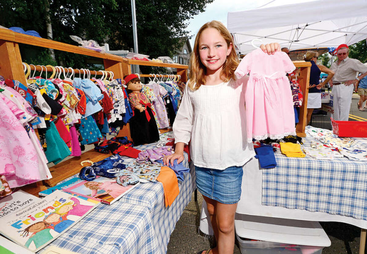 Hour photo / Erik Trautmann Grace Cristini, 10, pick out a dress for her doll during the 3rd annual Wilton Street Fair and Sidewalk Sale in Wilton Center Saturday.