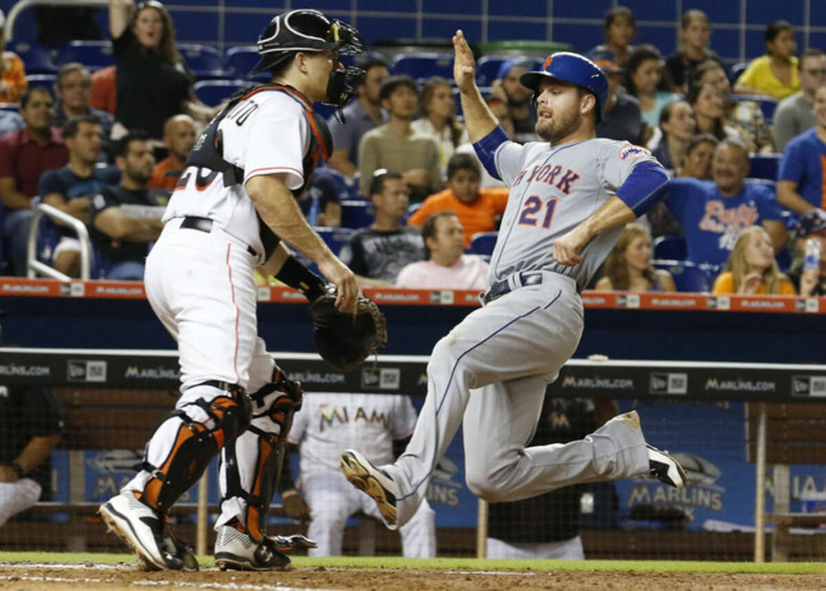 New York Mets first baseman Lucas Duda runs to home plate to score on a single by Eric Campbell in the eighth inning as Miami Marlins catcher J.T. Realmuto waits for the late throw during a baseball game in Miami, Tuesday Aug. 4, 2015. (AP Photo/Joe Skipper)