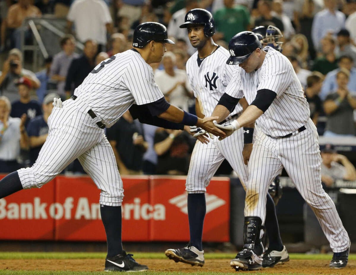 New York Yankees' Alex Rodriguez, left, celebrates with Brian McCann after Rodriguez and Chris Young, center, scored on McCann's seventh-inning home run in a baseball game against the Boston Red Sox at Yankee Stadium in New York, Tuesday, Aug. 4, 2015. (AP Photo/Kathy Willens)